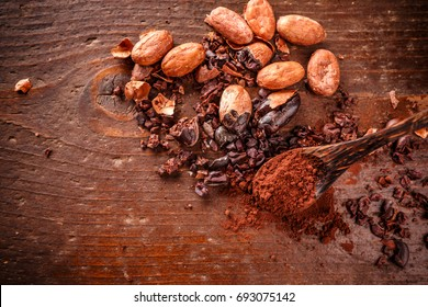Composition of cacao nibs, cacao beans and cacao powder on old wooden background
