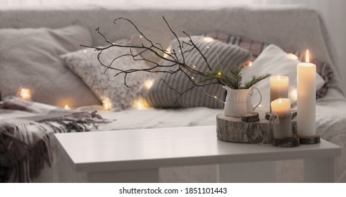 Composition of candles on  white table against the background of  sofa with plaids and pillows. Cozy home concept
