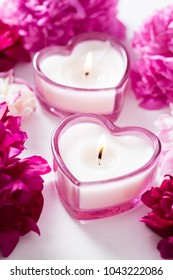 Composition with candles in the shape of a heart and rose petals
