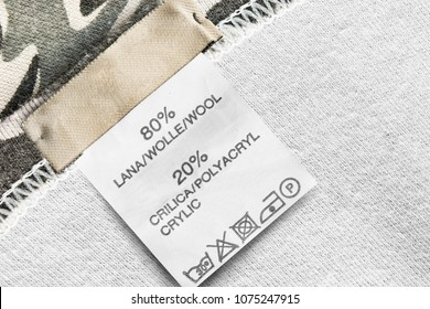 Composition and care clothes label on knitted khaki background closeup