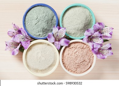 Composition of ceramic bowls with different types of sea clay powder: white, pink, green and blue and fresh flowers; concept of facial and body treatment; upper viewpoint