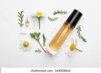 Composition with chamomile flowers and cosmetic bottle of essential oil on white background, top view