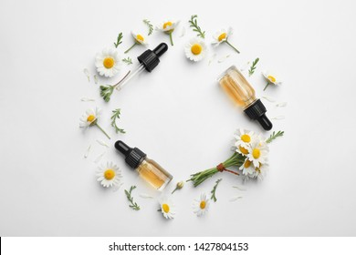 Composition with chamomile flowers and cosmetic bottles of essential oil on white background, top view. Space for text