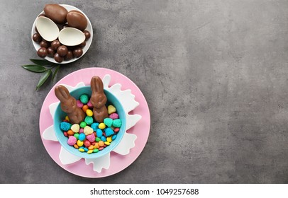 Composition with chocolate Easter bunnies and candies on gray background