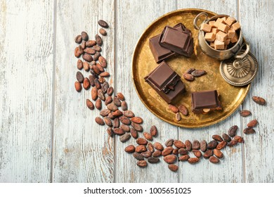 Composition with chocolate, sugar and cocoa beans on wooden background