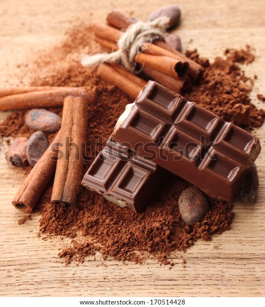 Composition of chocolate sweets, cocoa and  spices on wooden background