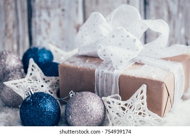 Composition with Christmas decorations and gift on white wooden background
