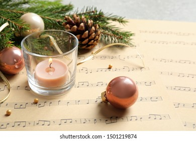 Composition with Christmas decorations and music sheets on table