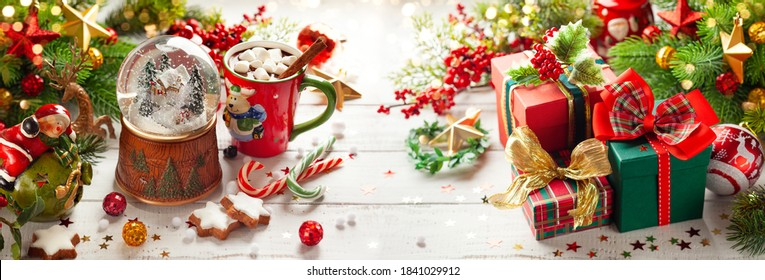 Composition with Christmas snow globe, gift boxes, cup of hot chocolate and festive decorations on wooden table. Christmas or New Year concept - Shutterstock ID 1841029912