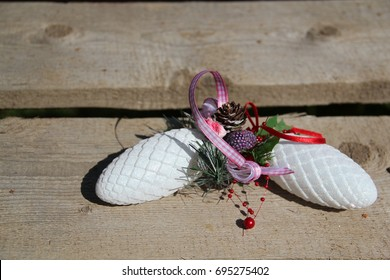 Composition of Christmas toys (sparkling white fir cones, lilac ribbon, strip, green needles) on a wooden background.  Concept: holidays - New Year, Christmas, magic