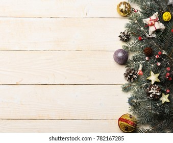 Composition of Christmas tree decor, copy space. Winter time and New Year card concept. Toys, balls and stars decorate fir tree branches. Christmas decorations on white wooden texture background.