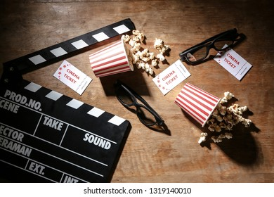 Composition with cinema clapperboard and popcorn on wooden background