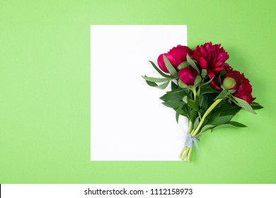Composition of clean sheet of paper decorated with marooned peonies flowers on green  background with copy space. Top view, Flat lay.