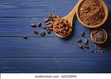 Composition with cocoa beans and powder on wooden background