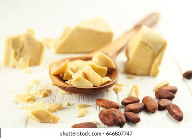Composition with cocoa butter and beans on wooden background