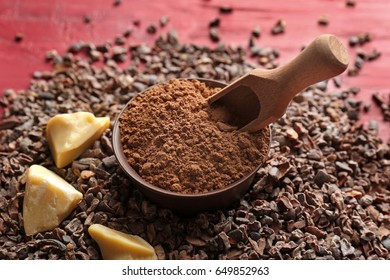 Composition with cocoa nibs, butter and powder on wooden background