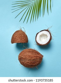 Composition from coconut and palm leaf in the form of a face with a closed eye on a blue background with copy space. Flat lay