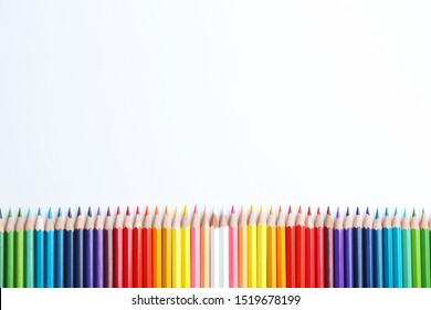 Composition with color pencils on white background, flat lay. Space for text