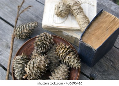 Composition of cones, an old book, a skein of yarn and ceramics gray wooden background. Background on a postcard