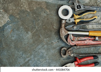 Composition of construction tools on an old battered concrete surface consisting of insulating tape, pliers, pipe wrench, screwdriver, industrial stapler, hammer, metal shears