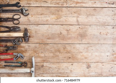 Composition of construction tools on an old battered wooden surface: pliers, pipe wrench, screwdriver, hammer, metal shears, saws.