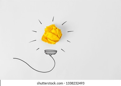 Composition with crumpled paper ball, drawing of lamp bulb and space for text on white background, top view. Creative concept