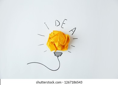 Composition with crumpled paper as lamp bulb and word IDEA on white background