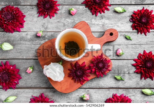Composition with cup of tea and beautiful flowers on wooden background