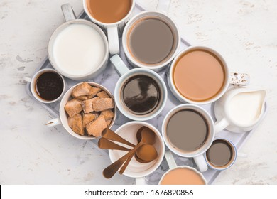 Composition with cups of different coffee on light background