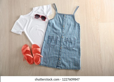 Composition with cute white kid t-shirt, sundress and shoes on wooden background
