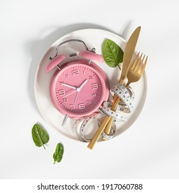 Composition with cutlery, measuring tape and alarm clock on white background. Diet concept