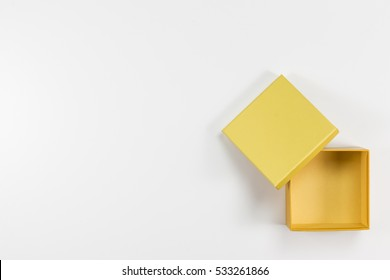 The Composition of Decorative Open, Small Flat, Yellow Box on White Background. Top View.