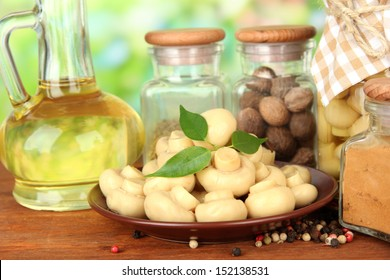 Composition of delicious marinated mushrooms, oil and spices on wooden table on bright background