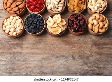 Composition of different dried fruits and nuts on wooden background, top view. Space for text