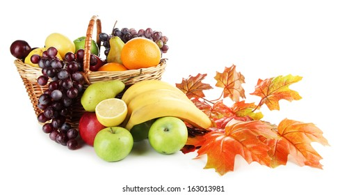 Composition of different fruits with basket and yellow leaves isolated on white