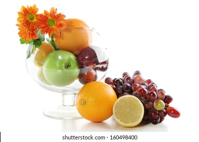Composition of different fruits with glass vase and flowers isolated on white