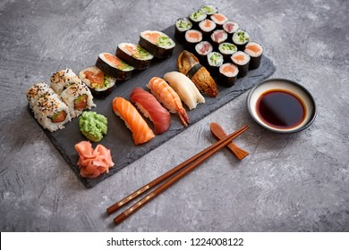 Composition of different kinds of sushi rolls placed on black stone board. Chopsticks and soy sauce bowl on side. Top angle view.