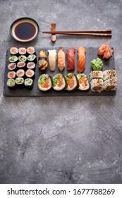 Zusammensetzung verschiedener Sushi-Rollen auf schwarzem Steinbrett. Stöckchen und Sojasauce auf der Seite. Draufsicht