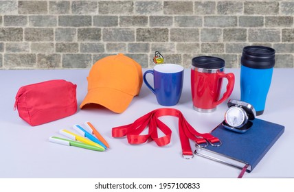 Composition of different promo products with rich colors -Thermo mugs, Lanyards Neck Strap, pens, mug, silver table office clock, zipped coin purse fabric, notebook,cap On desk grey and background gre - Shutterstock ID 1957100833
