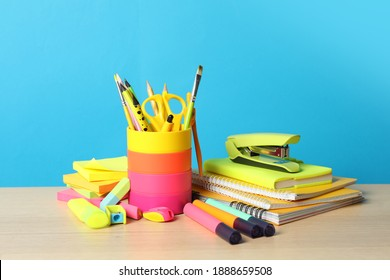 Composition with different school stationery on wooden table against light blue background. Back to school