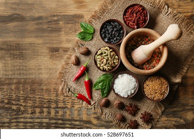 Composition with different spices and mortar on wooden background