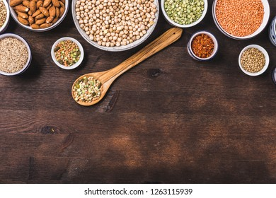 Composition of different types of legumes in bowls on wooden background