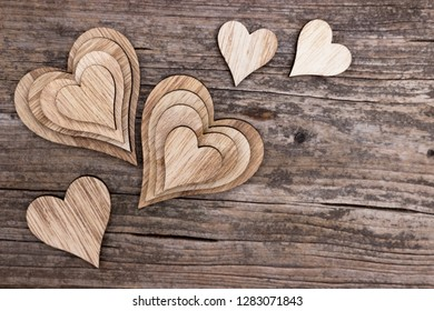 Composition of different wooden hearts on old wood