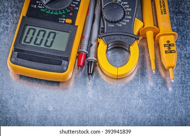 Composition of digital clamp meter electrical tester multimeter on metallic background electricity concept.