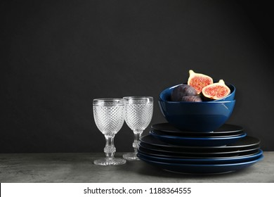 Composition with dinnerware on table against dark background, space for text. Interior element