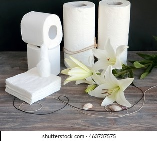 Composition of disposable paper hygienic products on wooden table against black background with lilies and sea shells. Concept of purity and spa.