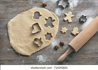 Composition with dough for Christmas cookies on wooden table