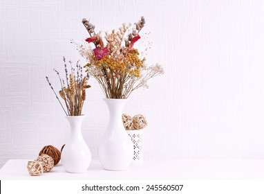 Composition of dried flowers on white wall background