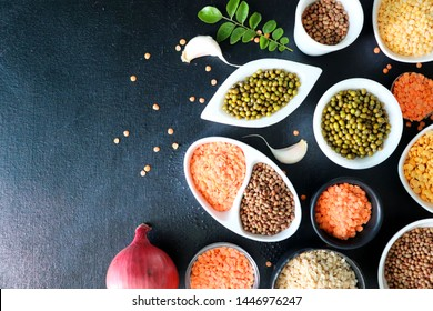 Composition of dry legumes. Assortment of colorful legumes in bowls. Lentils, Moth beans, Mung Beans, Masoor or red lentils, Split Chickpea, Toor Dal, Raw Split Mung Bean Lentils, Yellow Split.