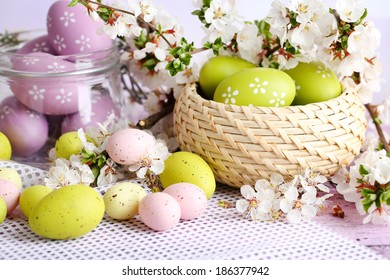 Composition with Easter eggs in glass jar and wicker basket, and blooming branches on light background
